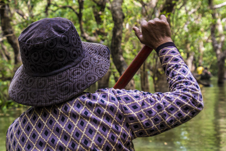 Rear view of man wearing hat while holding oar in lake at forest