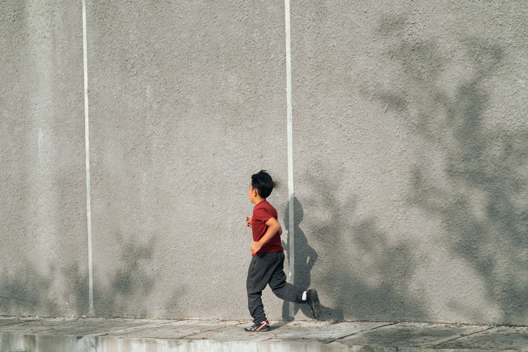 Full length of boy jogging against wall outdoors