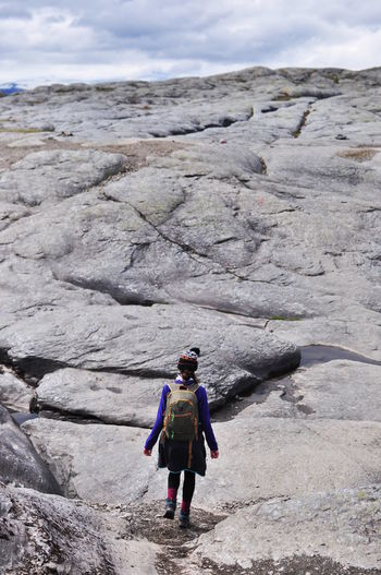 Rear View Of Backpack Woman Walking On Rock Formation