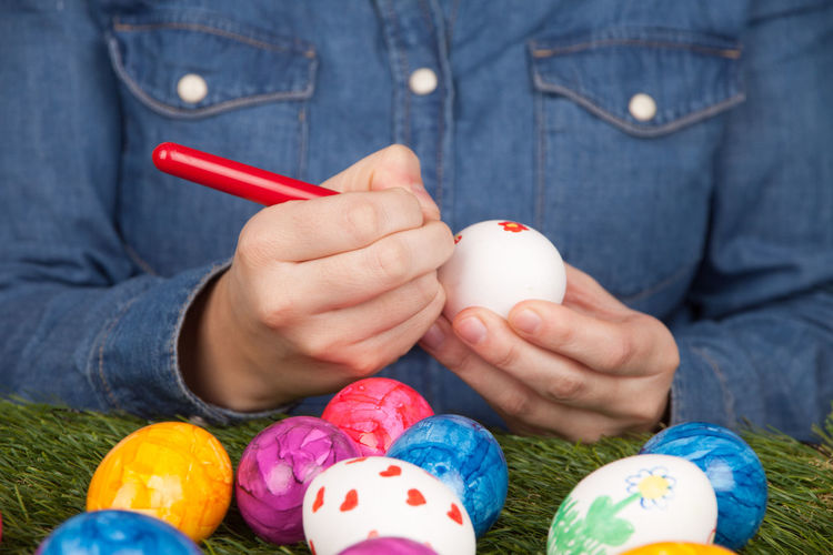 Midsection of woman coloring easter eggs