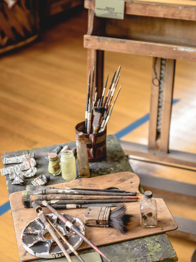 High angle view of paint equipment on wooden table