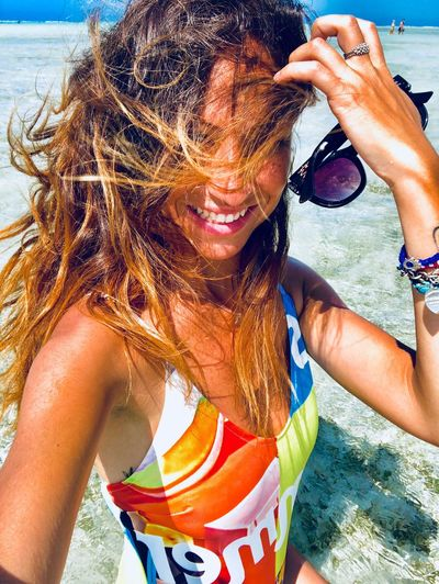 Women Leisure Activity Water One Person Beach Lifestyles Real People Land Front View Sunlight Day Nature Females Sea Three Quarter Length Swimwear Portrait Adult Outdoors