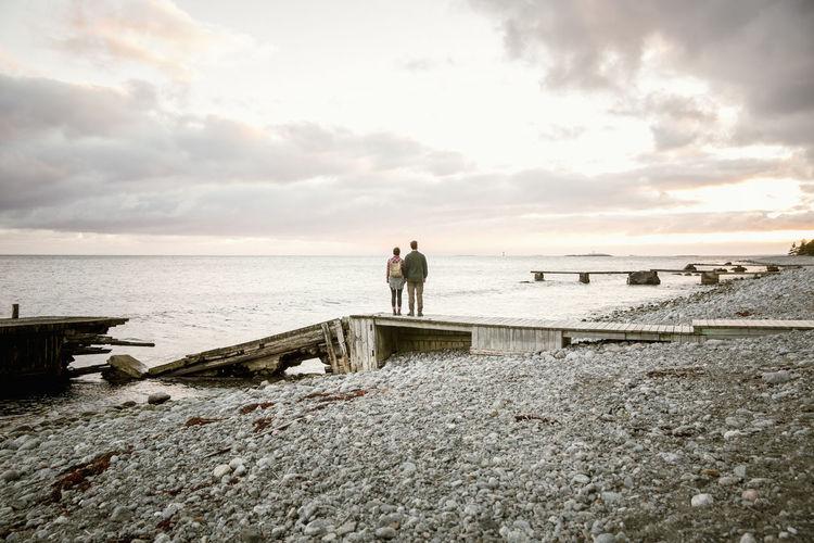 Men on rock by sea against sky