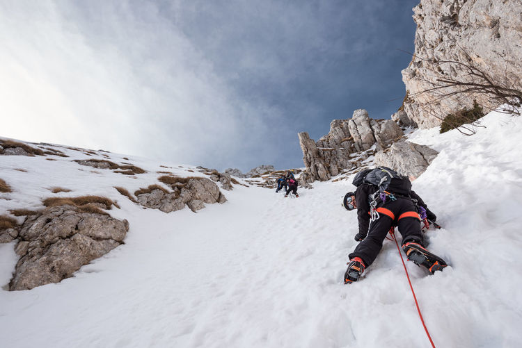 Low angle view of people climbing snow covered mountain against sky
