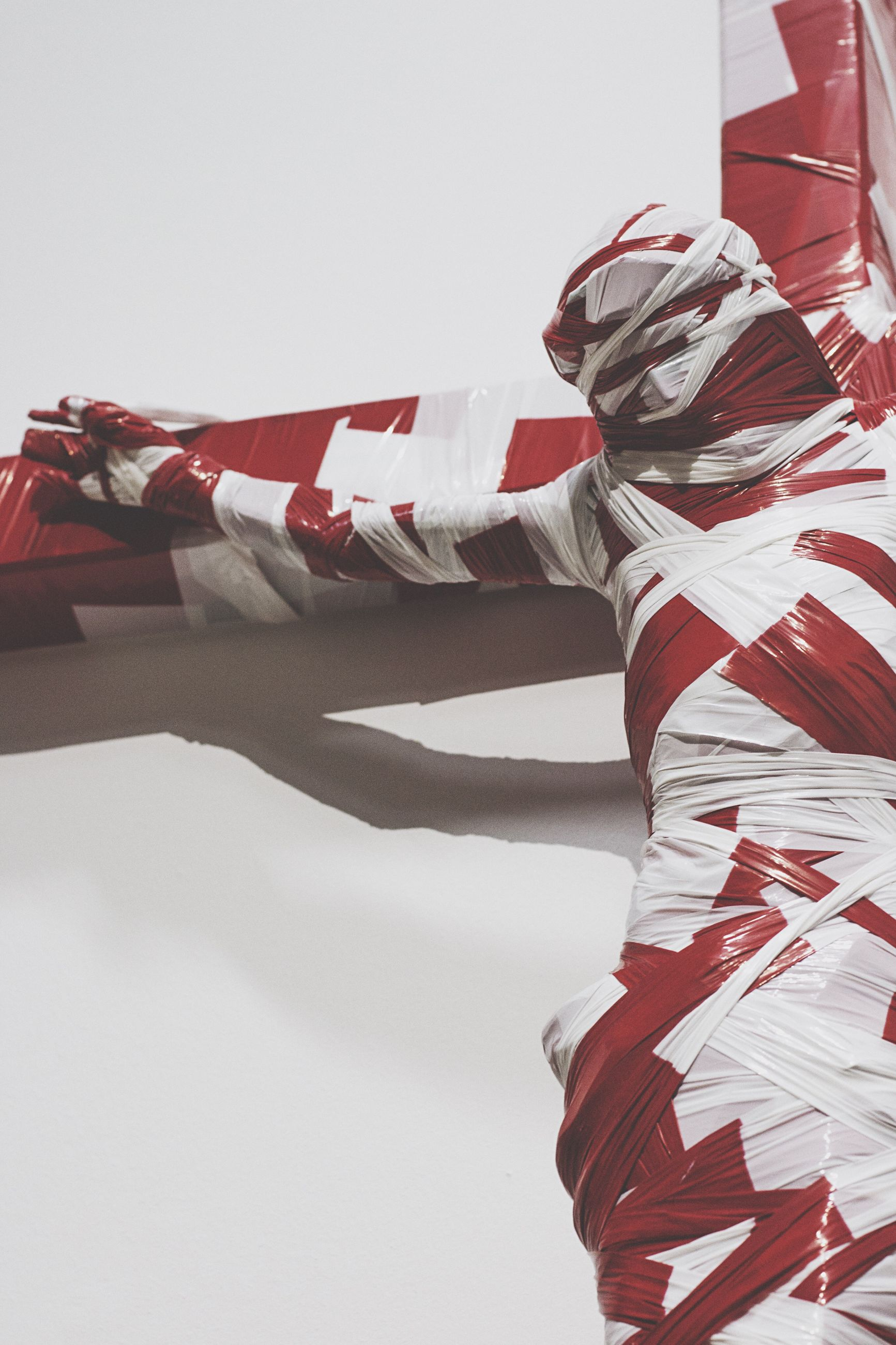 patriotism, identity, flag, national flag, low angle view, american flag, striped, architecture, built structure, red, fabric, white color, one person, building exterior, textile, culture, clothing, art and craft, creativity, copy space