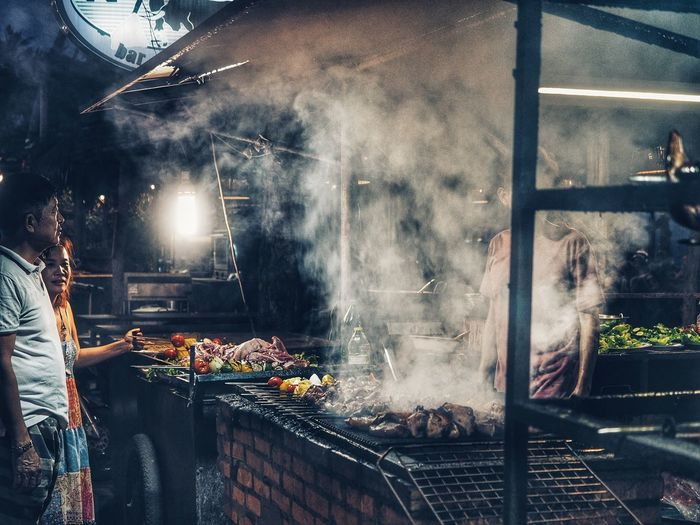 Food Smoke - Physical Structure Food And Drink Preparing Food Meat Preparation  Freshness Barbecue People Barbecue Grill Market Real People Grilled Business Heat - Temperature Group Market Stall Restaurant Illuminated Roasted Outdoors Street Food Chef
