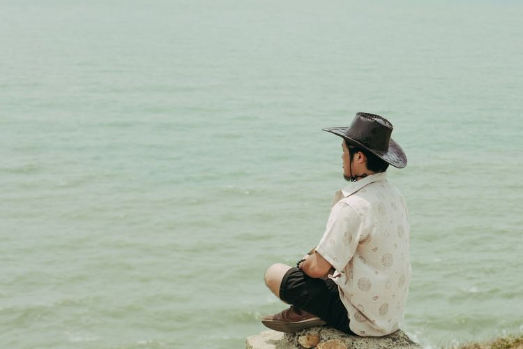 Mid adult man doing meditation while sitting at beach