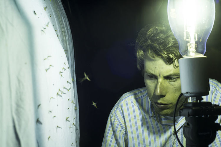 Portrait of man photographing illuminated electric lamp