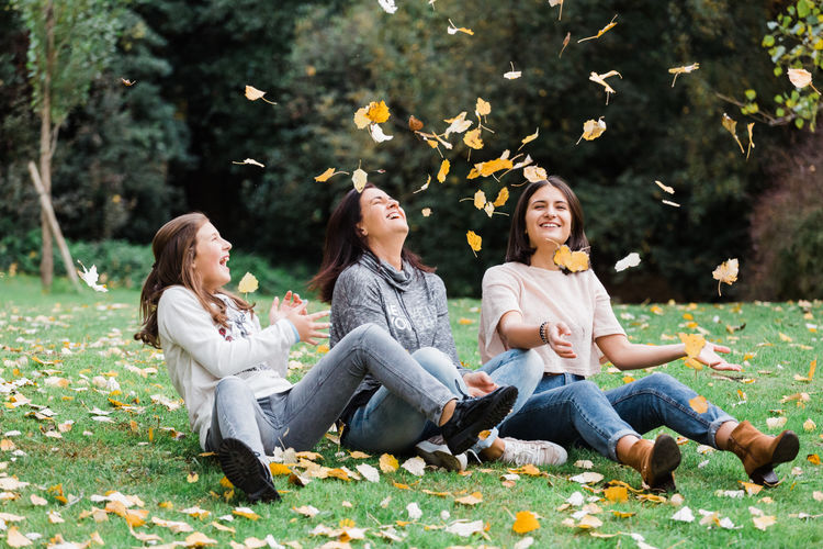 Adult Autumn Beauty Beauty In Nature Casual Clothing Cheerful Enjoyment Females Flower Fun Grass Happiness Leaf Nature Outdoors Park - Man Made Space People Relaxation Sitting Smiling Togetherness Tree Women Young Adult Young Women