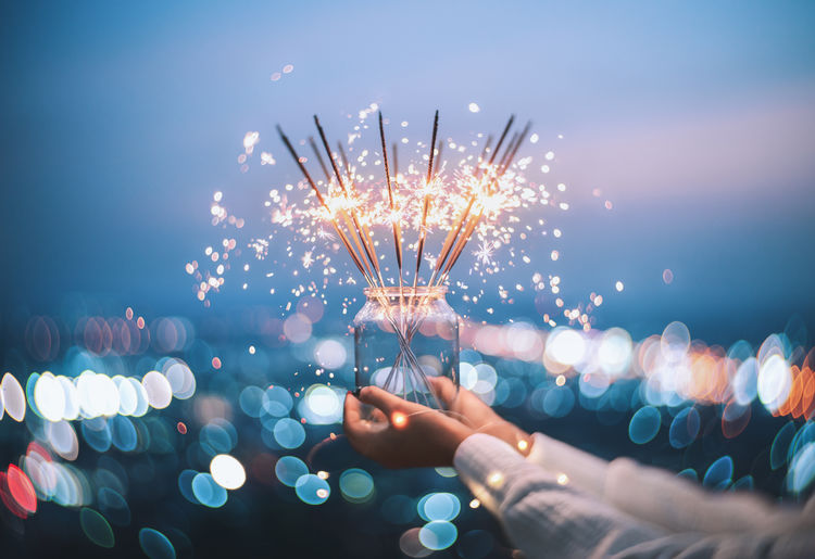 Cropped woman hands holding sparklers in jar at night
