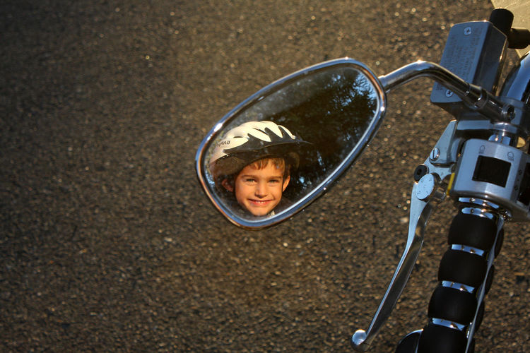 Reflection of boy on side-view mirror