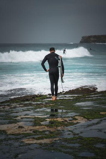 Full length of surfer  standing on rocks against sky