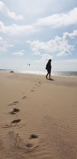 Woman walking at beach against sky
