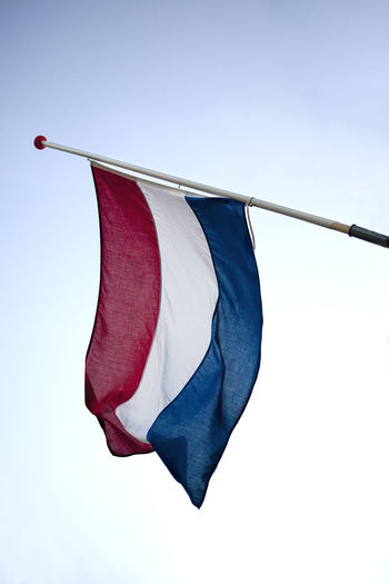 Low angle view of dutch flag against sky