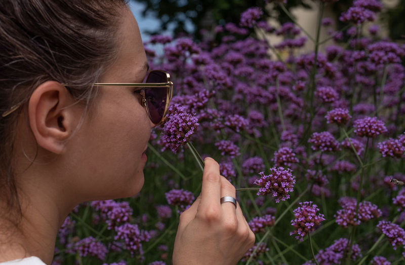 Close-Up Of Woman Smelling Purple Flowering Plants