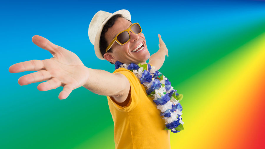 Portrait Of Excited Man Wearing Sunglasses And Floral Garland While Screaming Against Colored Background