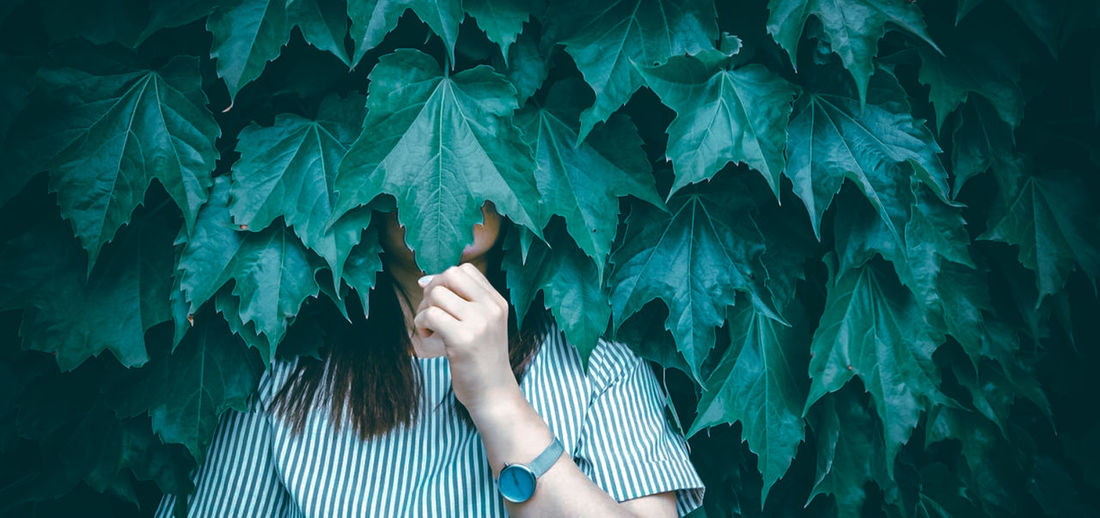 Low section of woman standing by leaves