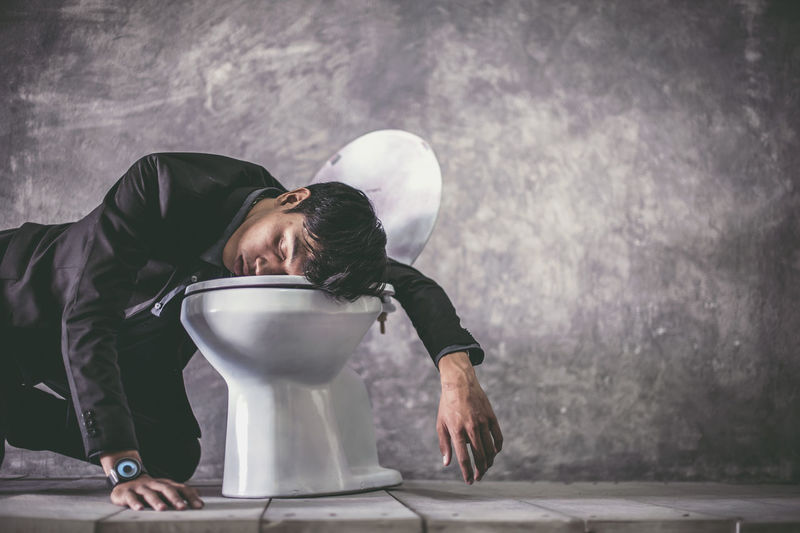 Man falling on toilet bowl in bathroom