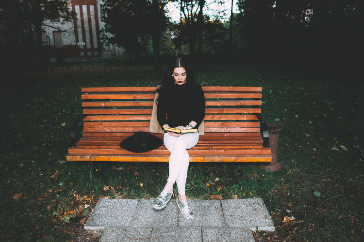 Portrait of young woman sitting on bench in park