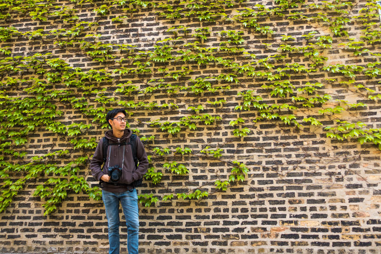 Man with camera looking away while standing against brick wall