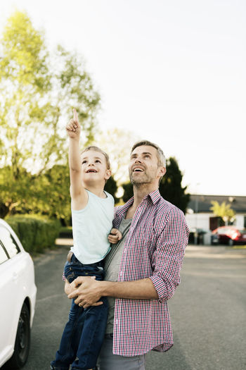Full length of father and daughter holding hands in car