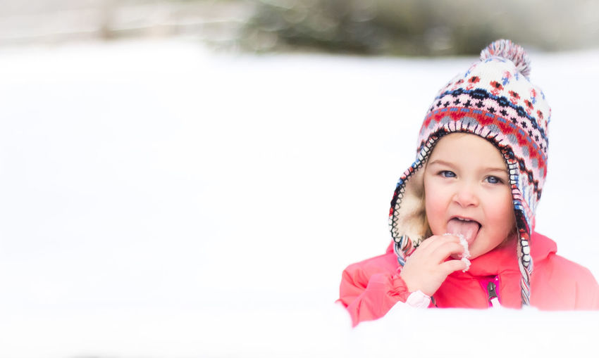 Portrait Of Cute Girl On Snow Covered Field During Winter
