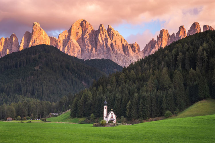 Beautiful alpenglow during sunrise in The Dolomites, Italy. Alps Mountain Mountain Range Mountains Sunset Alpenglow WoodLand Forest Trees Grass Green Orange Church Chapel Italy Dolomites Dolomites, Italy Golden Hour Landscape Scenics - Nature Sky Tree Nature Johanneskirche