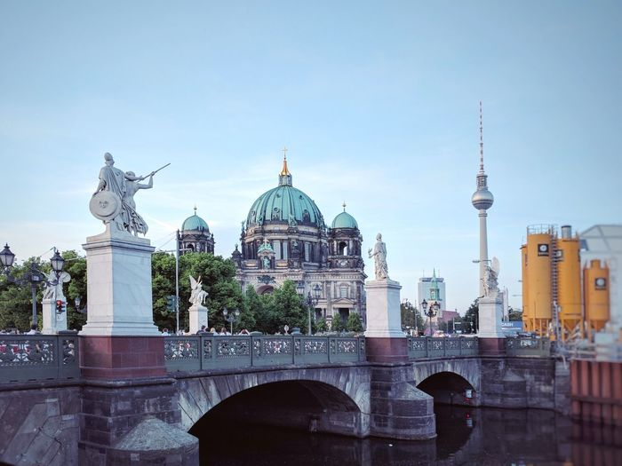 Sculptures on schlossbrucke bridge over spree river with berlin cathedral in background against sky