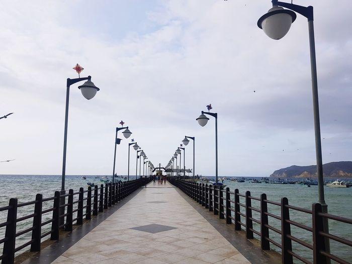 Street lights on pier by sea against sky