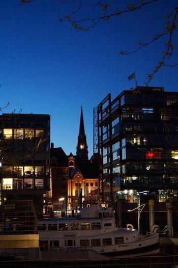 Illuminated buildings against blue sky at dusk
