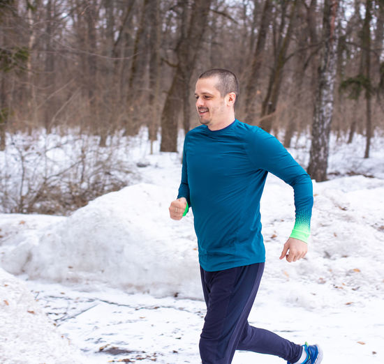 Runner man running outdoor in winter forest. Fitness and activity. One Person Tree Lifestyles Exercising Leisure Activity Three Quarter Length Day Land Sport Running Healthy Lifestyle Nature Men Forest Adult Young Adult Clothing Jogging Snow Winter Outdoors Runner Running
