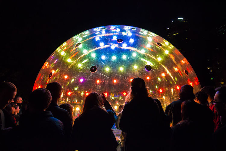 Rear View Of People Standing By Large Illuminated Ball In Nightclub