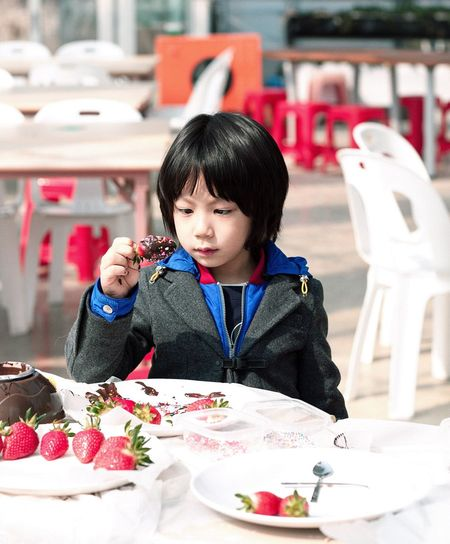 Young child holding chocolate covered strawberry at table