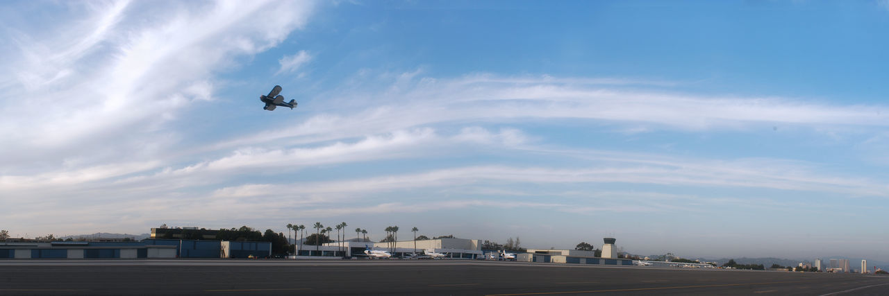 Biplane flying over santa monica airport against cloudy sky