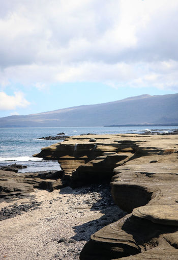 Beautiful rock formations on Santa Fe island, Galapagos Sky Water Cloud - Sky Tranquil Scene Land Scenics - Nature Beauty In Nature Sea Nature Beach Tranquility Rock Mountain Rock - Object Outdoors Galapagos Galapagos Islands Ecuador Santa Fe Rock Formation Formations Clouds Lava Ocean