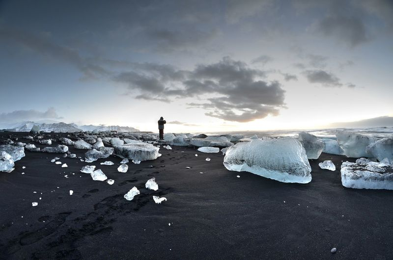 Man standing amidst ice blocks against sky at jokulsarlon