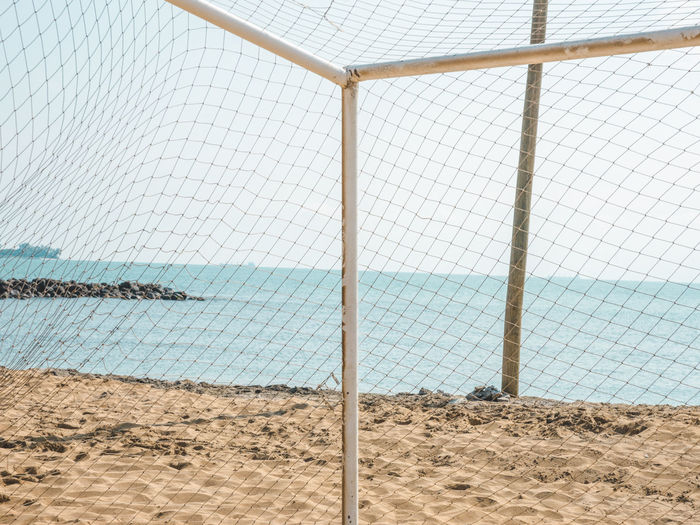 Close-Up Of Chainlink Fence On Beach Against Sky