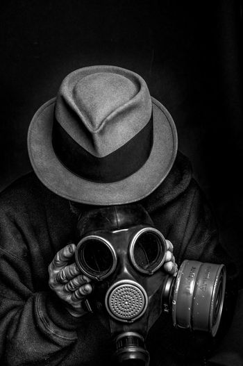 Close-Up Of Man Wearing Gas Mask Against Black Background