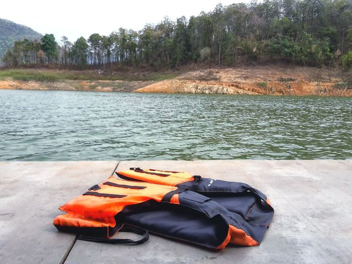 Aways wear a life vest before swimming. Safty Life Vest Life Jacket Dam Water Deep Tree Raft RaftingTrip Water Nature Outdoors No People Day Tree Beauty In Nature