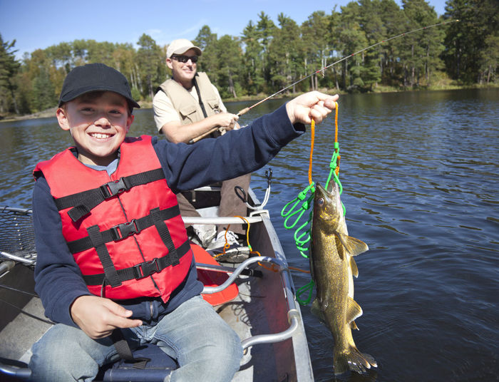 Smiling boy fisherman in a canoe holds up a stringer with nice walleyes Boy Fishing Smiling Fisherman Man Dad Happy Lake Walleye Minnesota USA Canoe Boat Water Pines Trees North Stringer Catch Net Outdoors Recreation  Fun Color Image Photography People Sunlight Life Preserver Autumn Hat Cap Sunglasses