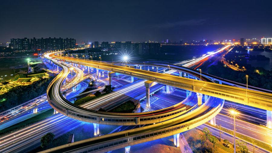 Illuminated multiple lane highway in modern city against sky
