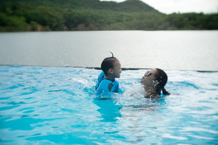 Mother and cute son enjoying in swimming pool