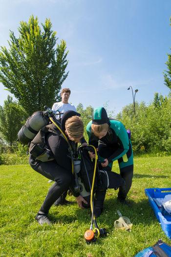 Scuba divers preparing their equipment on grassy field against clear sky