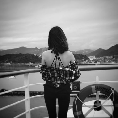 Rear View Of Woman Standing On Boat Against Sky