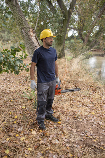 Full length of man holding chain saw standing in forest