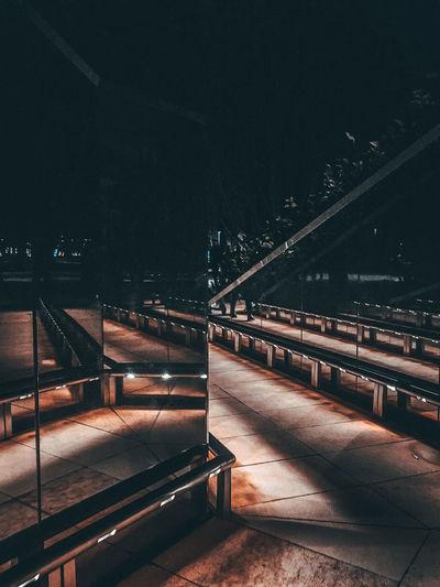 Empty footpath in illuminated city at night