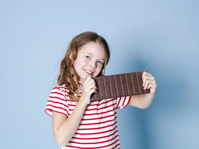 Girl Child Chocolate Bar BIG Huge Brown Sweet Hold Food Candy Nutrition Unhealthy Teeth Calories Nerves Happy Cocoa Reward Laugh Joy Posen Model Copy Space Concept Energy Sugar Ration Sweet Tooth Nibble Chomp Munch Delicious Good Addictive Intoxication Beautiful Looking At Camera Striped Portrait One Person Childhood Smiling Indoors  Front View Girls Casual Clothing Studio Shot Waist Up Holding Happiness Women Emotion Hairstyle Innocence Blue Background