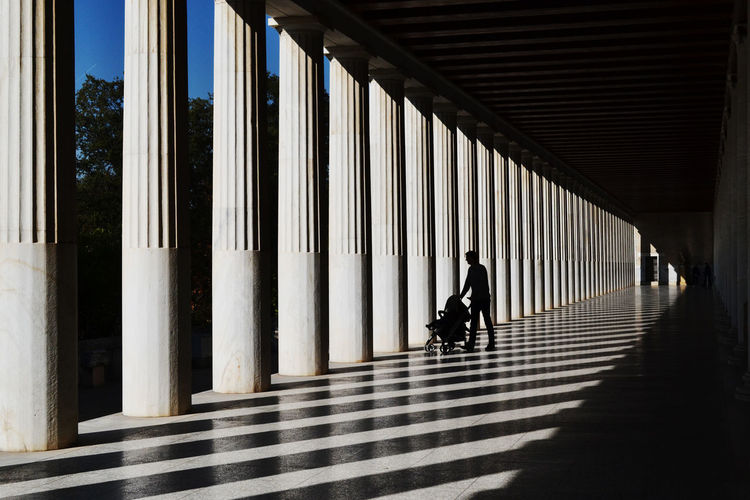 Man with baby stroller in colonnade
