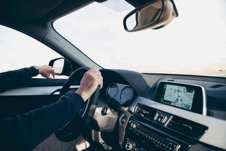 Man driving a luxury car. Interior view Mode Of Transportation Transportation Car Vehicle Interior Steering Wheel Land Vehicle Driving Motor Vehicle Car Interior Hand Human Hand One Person Real People Windshield Control Panel Human Body Part Driving Safety Luxury GPS Navigator  Trip Journey Road Highway