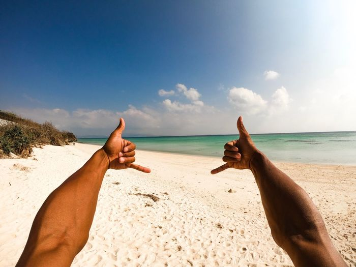 Man doing shaka sign on beach against sky